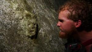 Arqueólogo Greg Schwab mirando una cara grabada en una cueva de la región de Nueve Cerros.  Foto tomada por Matt Oliphant.
